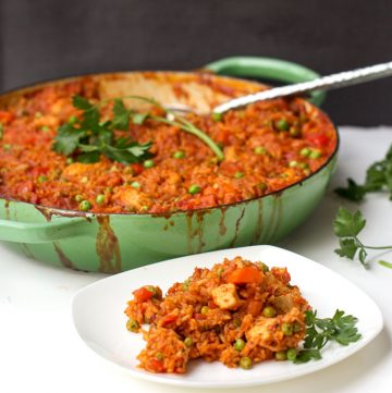 A shallow green casserole dish filled with jollof rice, a plate of jollof rice in front, both garnished with parsley