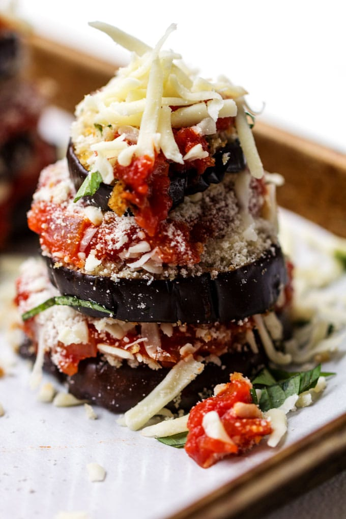 a stack of three eggplant rounds, layered with thick tomato sauce and shredded mozzarella cheese.