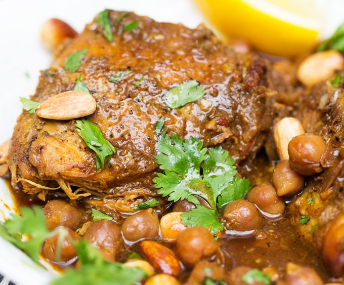 close up of a slow cooked chicken thigh surrounded by chickpeas and rich broth, topped with garnishes of toasted almonds and bits of cilantro and a lemon wedge