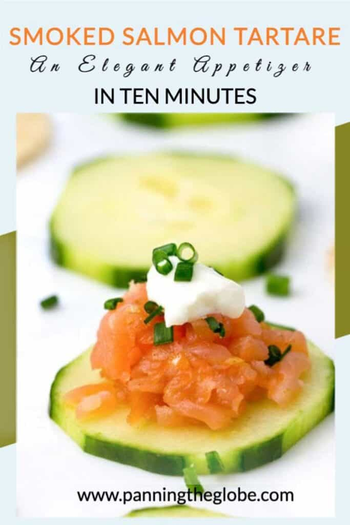 close up of a slice of cucumber topped with smoked salmon tartare, sour cream and chopped chives