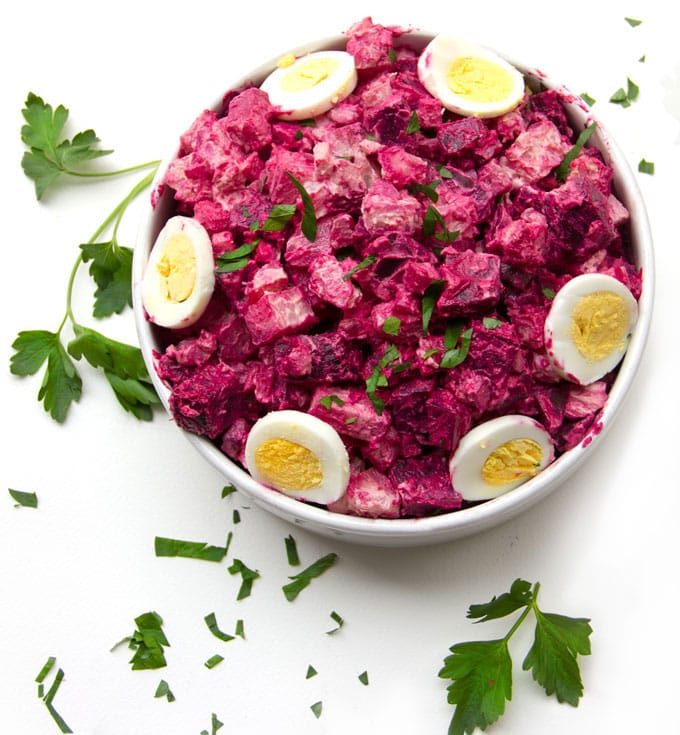 a bowl of hot pink potato salad with slices of hard boiled egg around the rim and garnishes of parsley on the white table surrounding