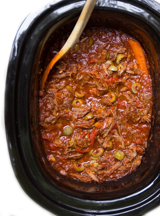 Ropa Vieja is a famously delicious Cuban stew of tender shredded beef with bell peppers, tomatoes, olives and spices. It's a perfect recipe for the slow cooker! Serve it with rice and black beans for a traditional cuban meal.