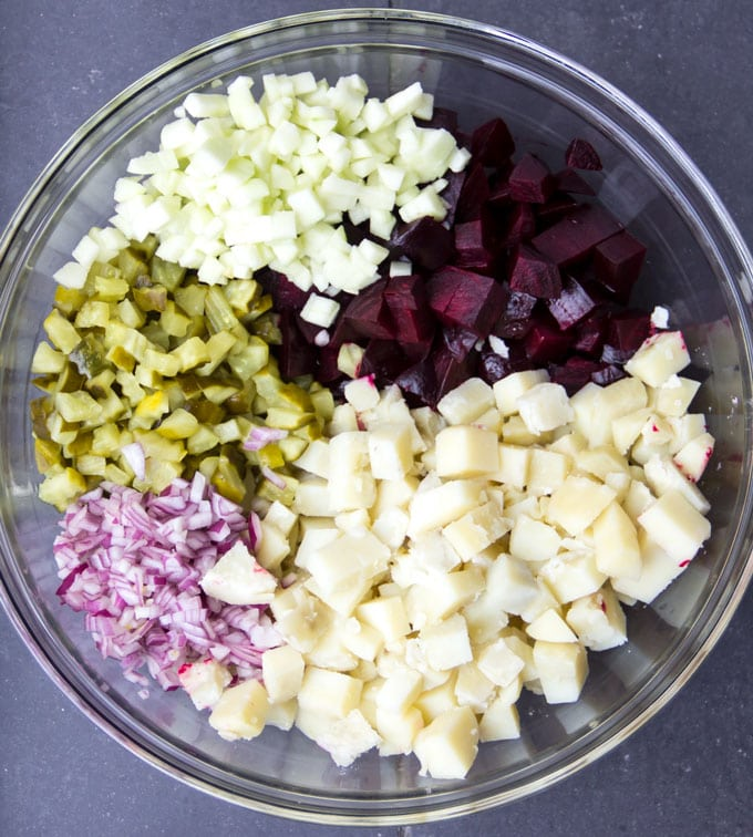 Glass mixing bowl filled with ingredients for Rosolje: a pile of chopped apples, pickles, onions, diced beets and diced potatoes