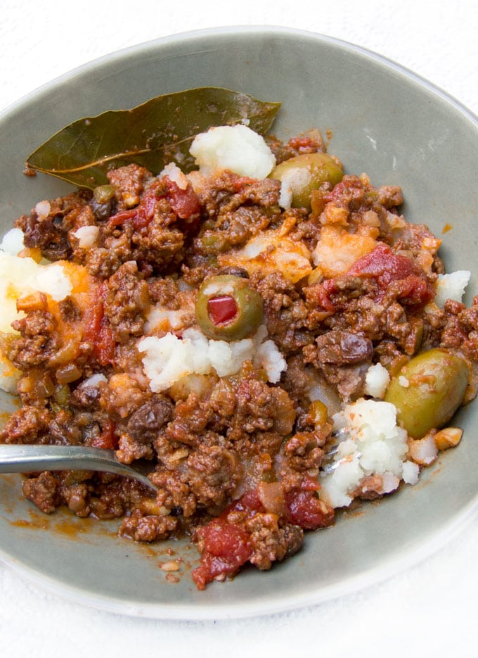 A bowl of Cuban Picadillo: sweet and sour ground beef stew in a flavorful tomato sauce with vinegar, onions, garlic, olives and smoked paprika. Served over mashed potatoes.