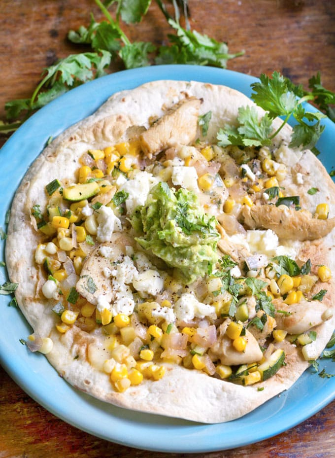 Chicken Tostada: Flour tortilla topped with chicken, corn, zucchini, feta and avocado salsa