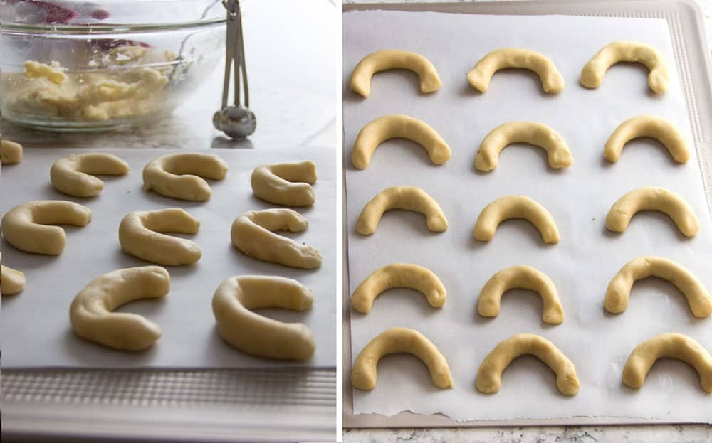A parchment-lined cookie sheet topped with 15 pieces of crescent-shaped cookie dough, ready to go into the oven to bake