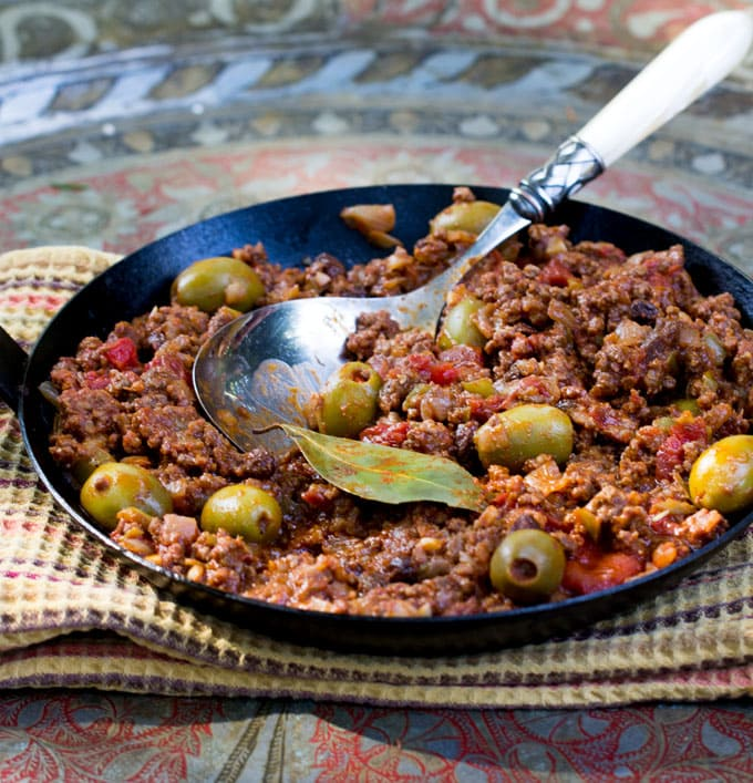 Cuban Picadillo. Sweet and sour ground beef stew in a flavorful tomato sauce with vinegar, onions, garlic, olives and smoked paprika. The recipe is quick and easy, 35 minutes start to finish.