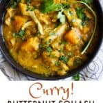 a black bowl filled with a stew of curry butternut squash, chicken and lentils