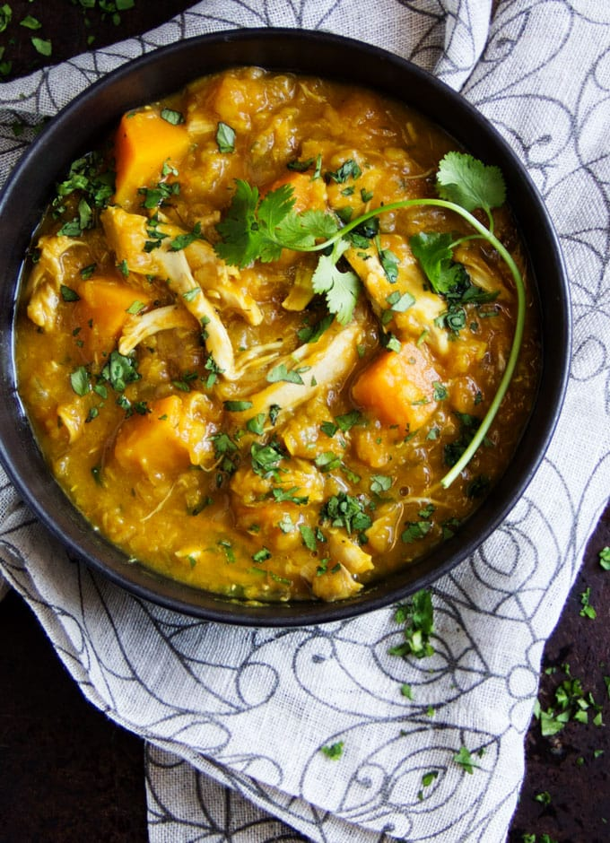 Bowl of curried butternut squash, lentil, and chicken stew with a sprig of cilantro.
