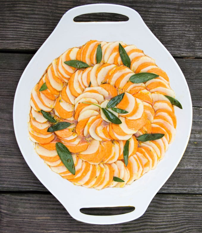 russet and sweet potato slices lined up in cocentric circles with sage leaves