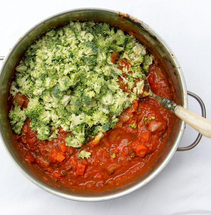 overhead shot of a sauce pot filled with sauce and half of it is covered with shaved broccoli