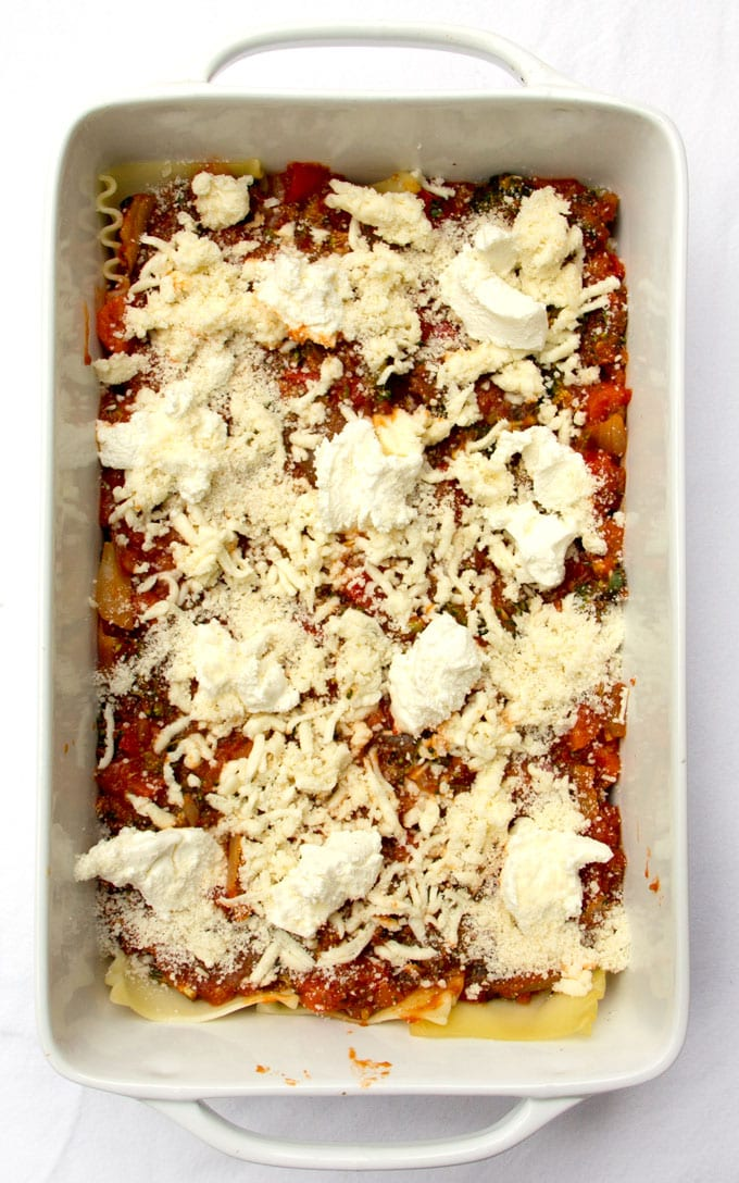Roasted vegetable lasagna in a white rectangular casserole dish shown from above before it's been baked