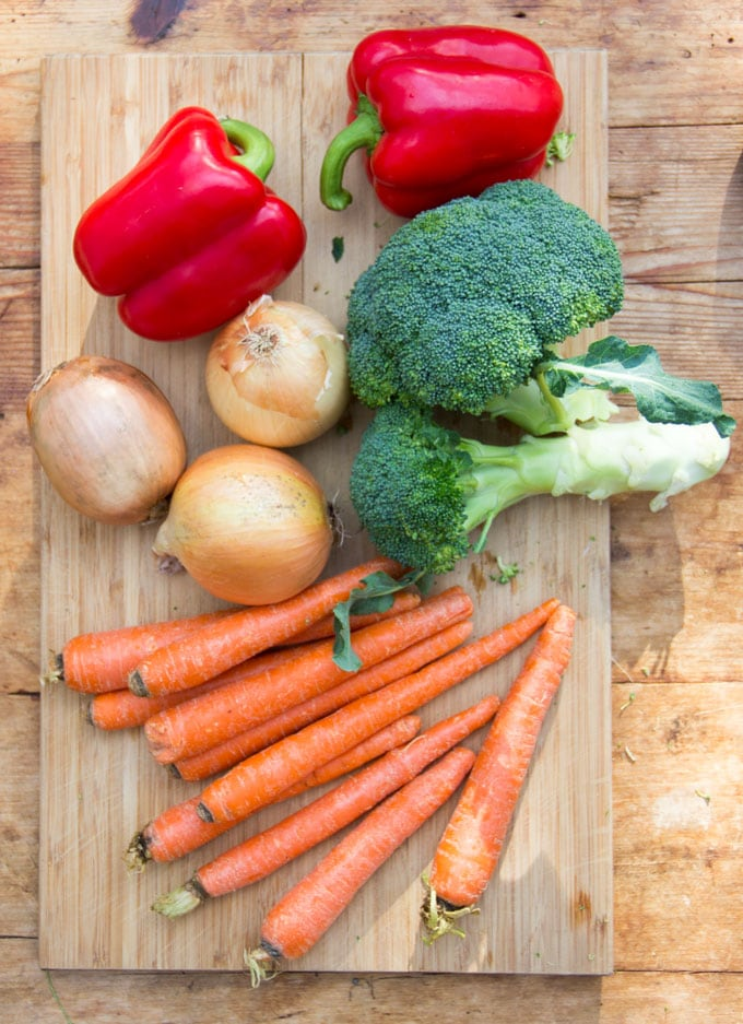 2 red bell peppers, 3 yellow onions, 1 bunch of broccoli and 10 carrots on a wooden cutting board.