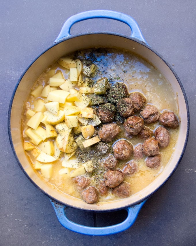 Blue Dutch oven filled with broth, cooked meatballs, diced potatoes, herbs and spices