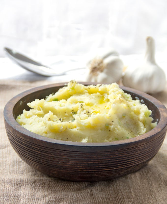 Brown wooden bowl filled with mashed potatoes. Two whole garlic bulbs in the background.