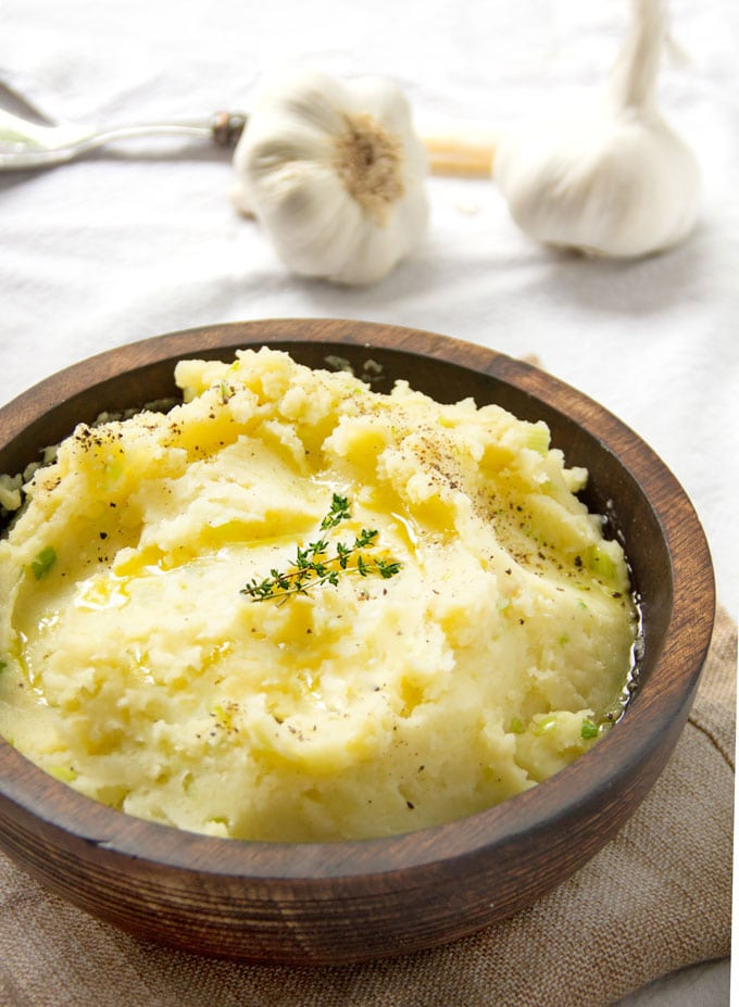 Brown wooden bowl filled with mashed potatoes and garnished with a sprig of thyme. Two whole garlic bulbs in the background.