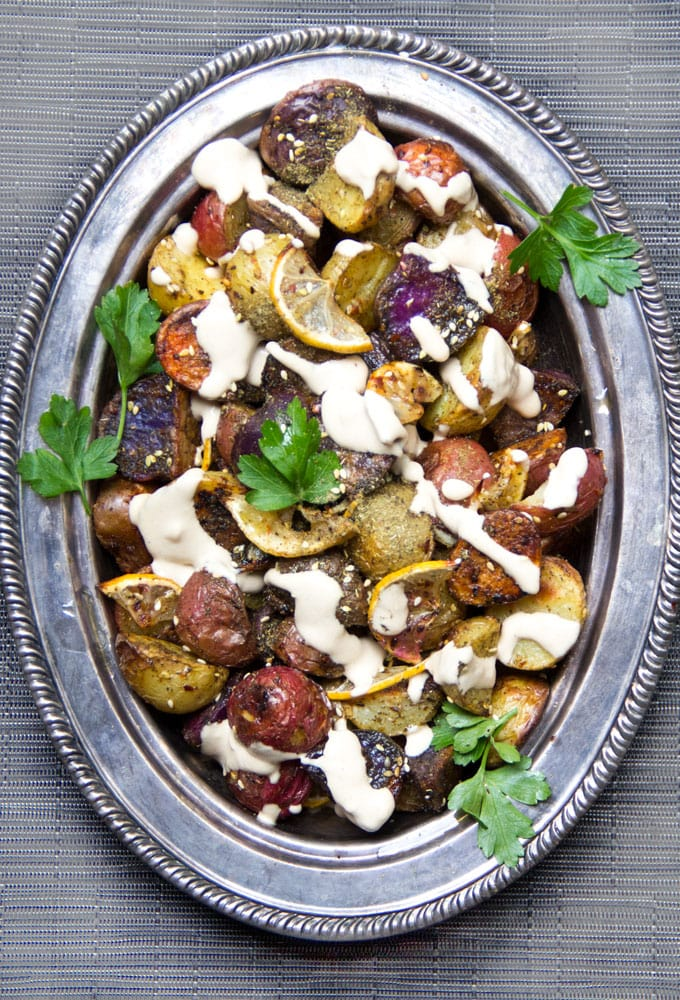 rainbow roasted potatoes on a silver platter drizzled with tahini and garnished with parsley