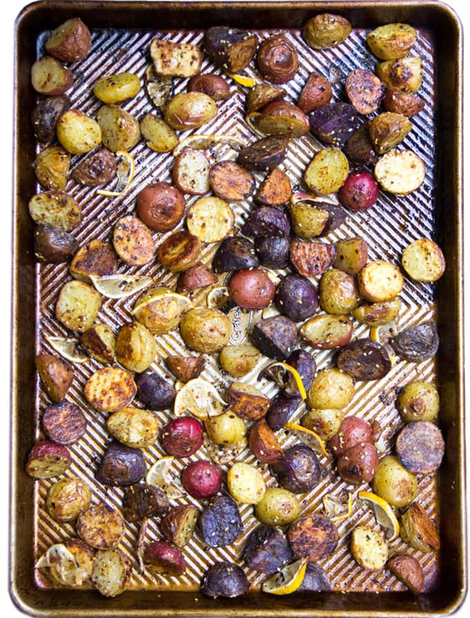 a rimmed baking sheet covered with halved roasted potatoes in different colors