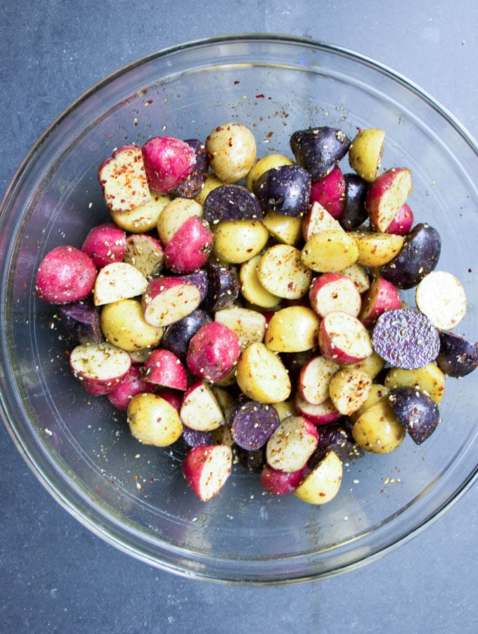 A glass bowl with rainbow colored raw Potatoes sliced in half and tossed with oil and Za'atar