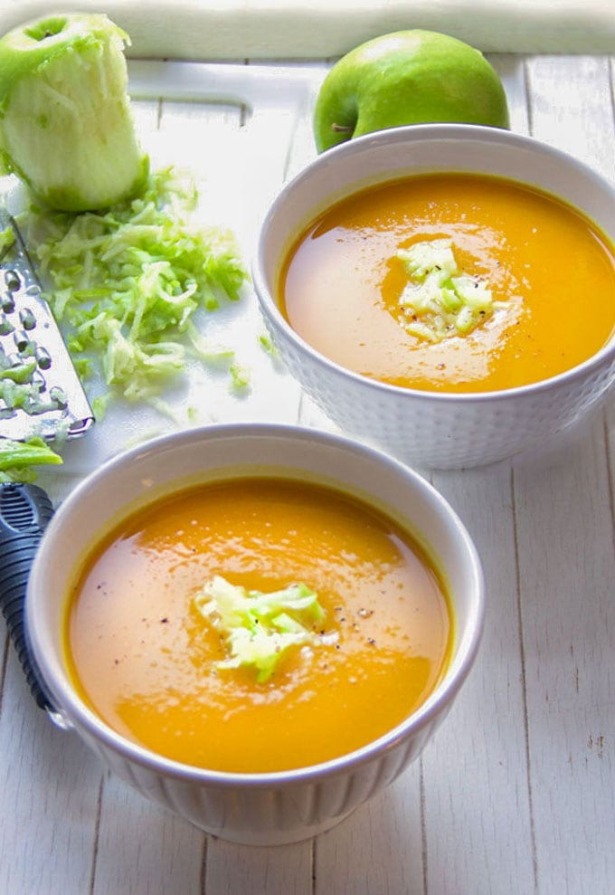 two bowls of curried butternut squash soup with shredded green apple garnhish