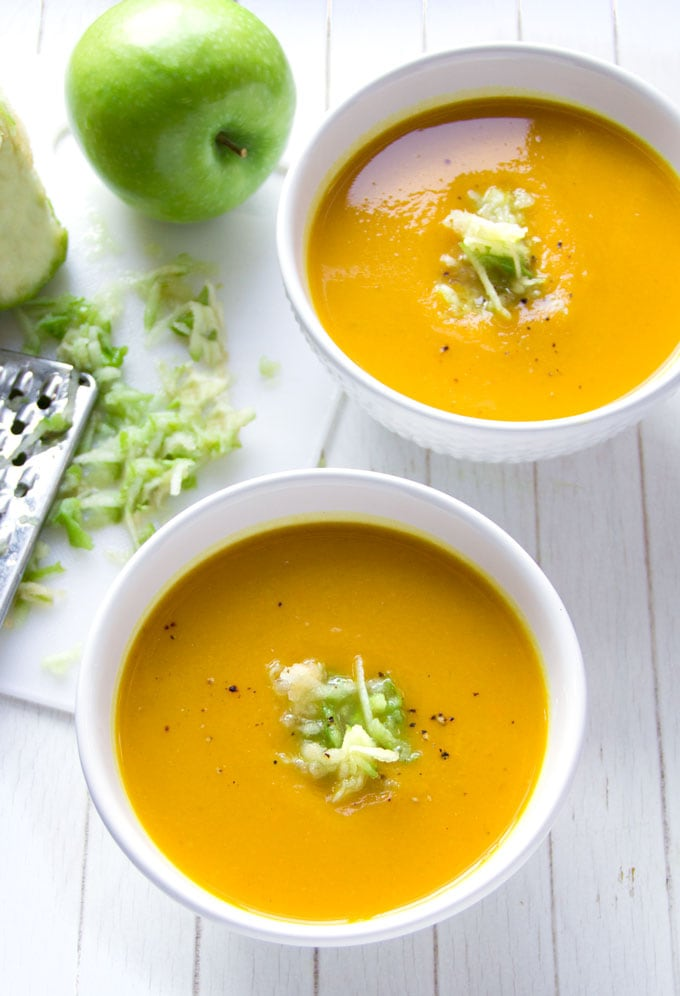 two bowls of curried butternut squash soup topped with shredded granny smith apples