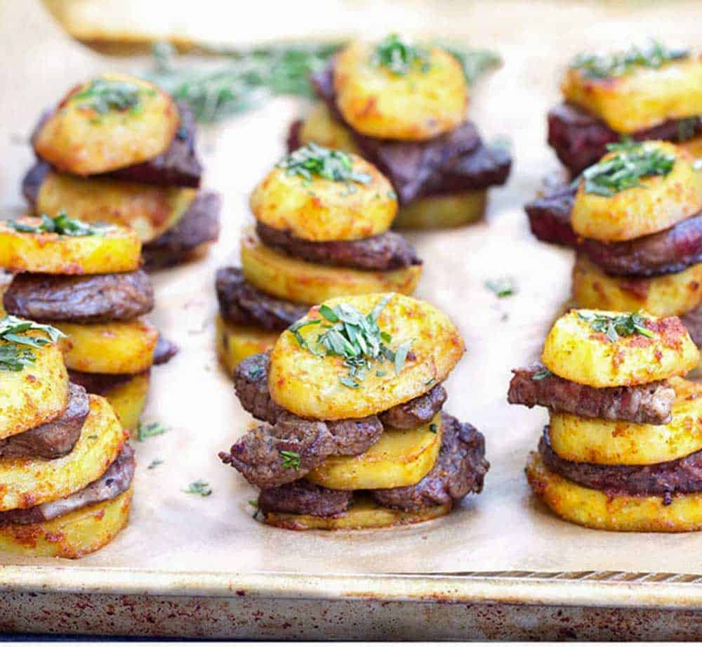 Baking sheet topped with rows of steak and potatoes stacks