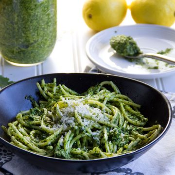 a black bowl filled with spaghetti and arugula pesto, with a jar of arugula pesto and two lemons in the background