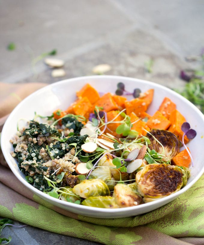 A sweet potato brussels sprout buddha bowl with roasted vegetables kale, quinoa, lemon dressing and a garnish of slivered almonds