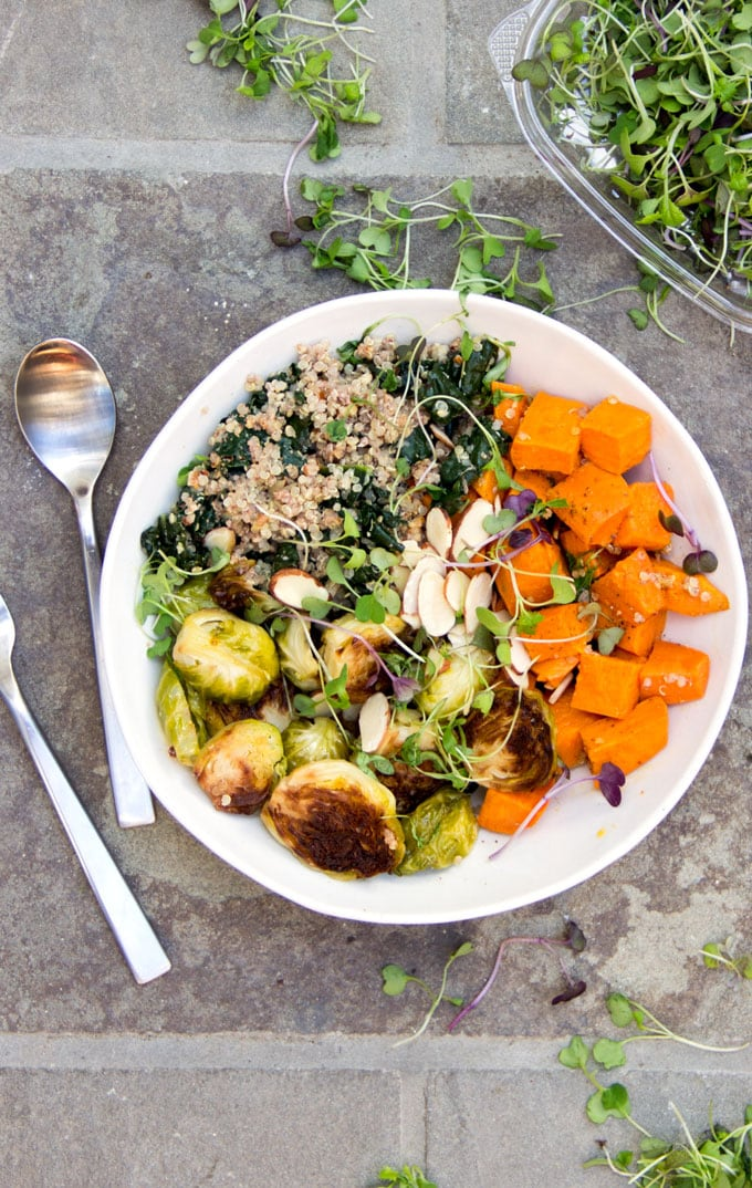 """A """"Buddha Bowl"""" is the ultimate satisfying nutritious meal, a bountiful bowl of beautiful, healthy, vegetarian ingredients. This sweet potato brussels sprout buddha bowl combines roasted vegetables kale, quinoa, and a luscious lemony dressing. Plus, it's gluten-free and vegan."""