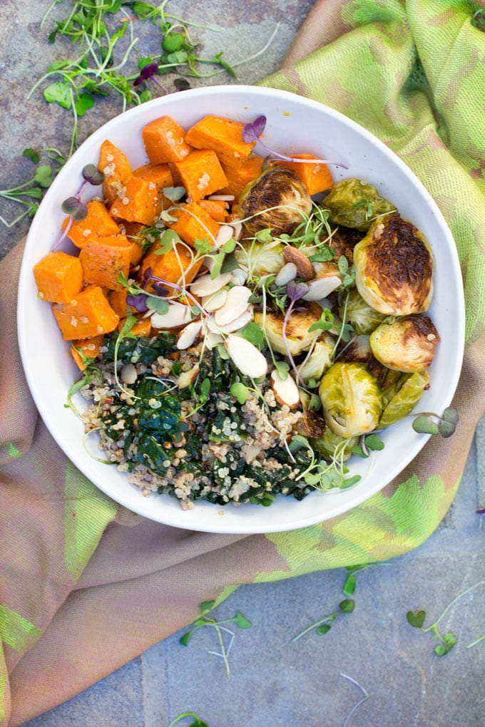 A buddha bowl on a green cloth napkin: A sweet potato Brussels sprouts buddha bowl with quinoa, wilted kale and a sprinkle of slivered almond and micro greens