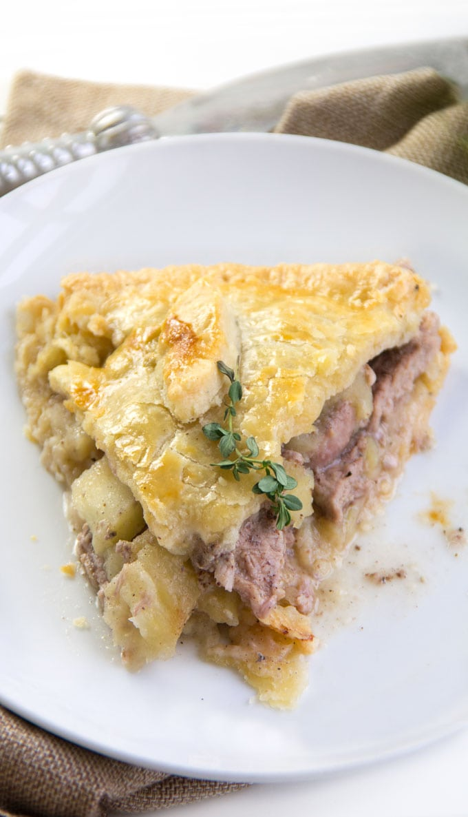 close up overhead picture of a slice of pork pie on a white plate with a thyme sprig on top