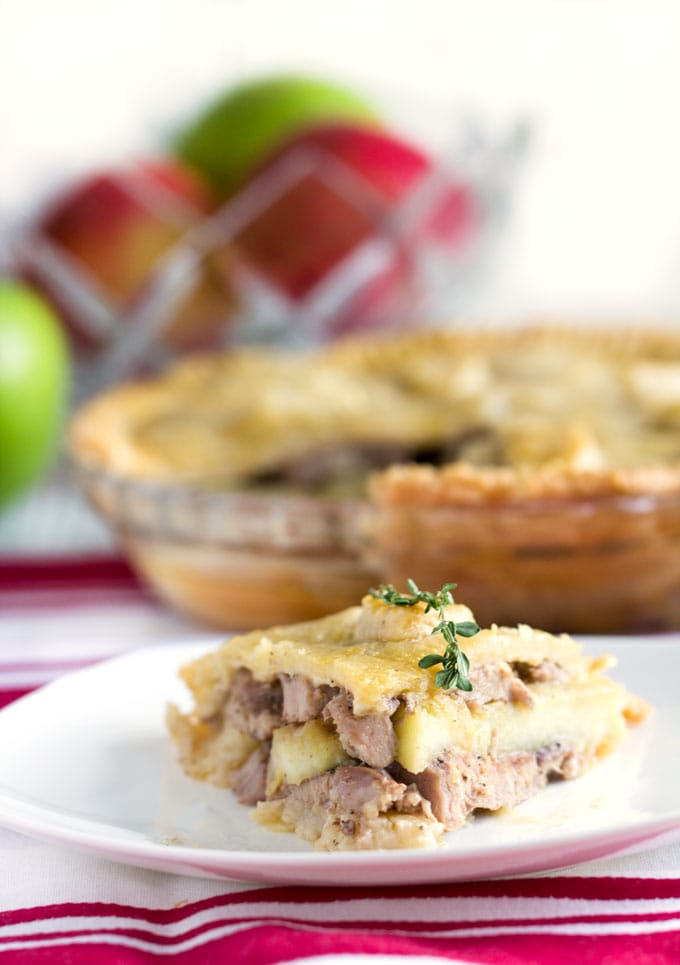 slice of cheshire pork pie in the foreground with the whole pie and a bowl of green and red apples in the background.