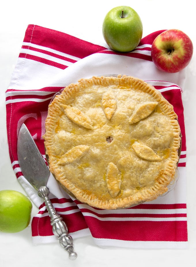 overhead shot of a whole cheshire pork pie on a red and white striped dish towel surrounded by two green apples and one red apple and a pie serving knife