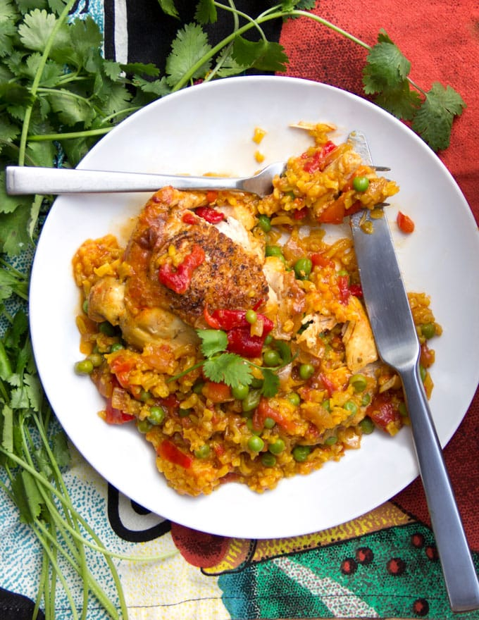 Arroz Con Pollo is Spain's beautiful and beloved chicken and rice casserole. It's a one pot wonder that emerges from the oven with tender chicken and yellow rice, in a flavorful sauce of aromatic vegetables, tomatoes, spices.
