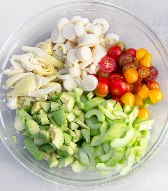 Ingredients for Brazilian hearts of palm salad: sliced hearts of palm, cucumbers, artichoke hearts, avocados and cherry tomatoes