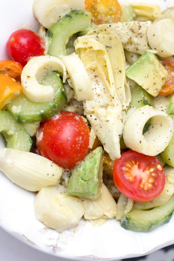 close up of hearts of palm salad with cucumbers, artichoke hearts and cherry tomatoes