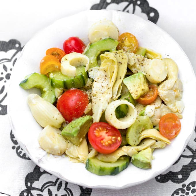 bowl with hearts of palm salad with cucumbers, artichoke hearts, avocados and cherry tomatoes