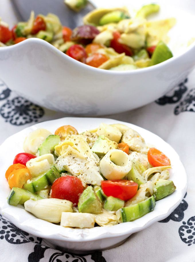 two bowls of hearts of palm salad with artichoke hearts, cucumbers and cherry tomatoes.
