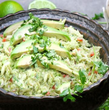 a dark metal bowl filled with Venezuelan avocado chicken salad garnished with 3 slices of avocado and chopped cilantroa dark metal bowl filled with Venezuelan avocado chicken salad garnished with 3 slices of avocado and chopped cilantro
