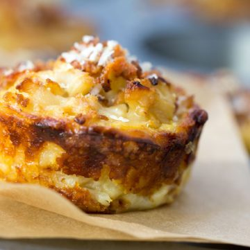 These savory cauliflower tarts are amazing little flavor bombs: potato-gruyere crusts filled with onions, garlic, cauliflower, eggs, cheese, and spices, topped with bacon and parmesan. A perfect recipe for a special brunch, with an easy vegetarian adaptation.