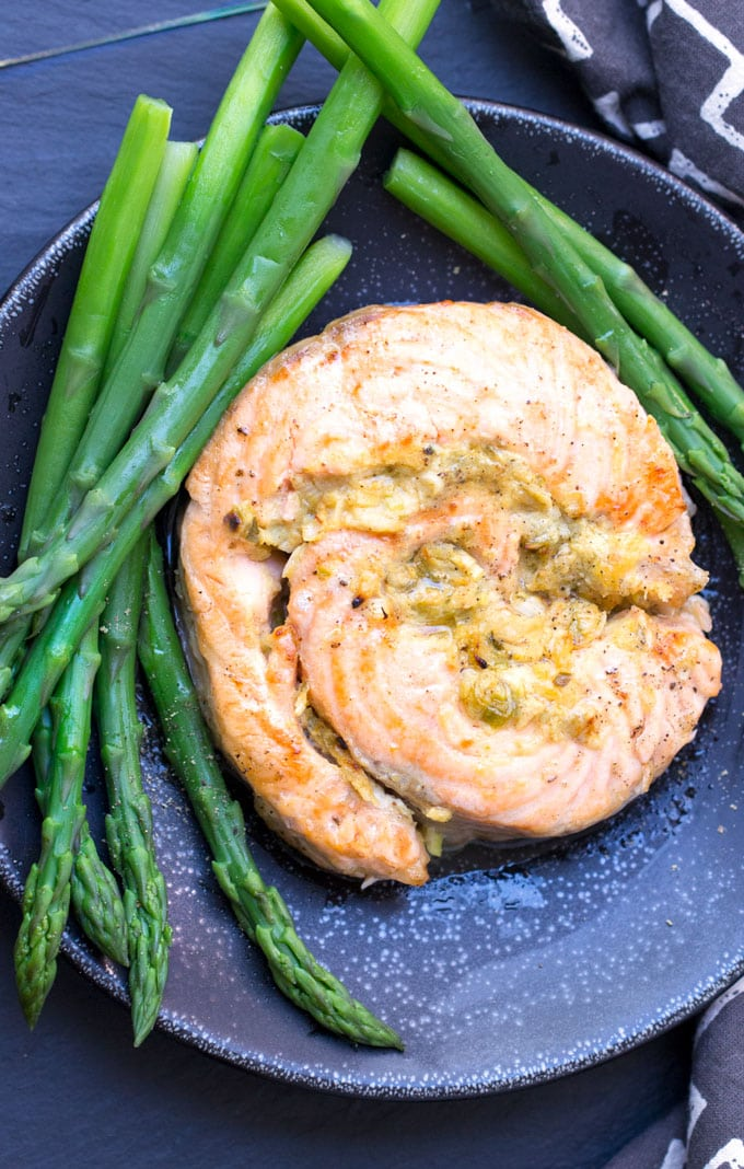 a black plate topped with a stuffed salmon roulade surrounded by steamed asparagus