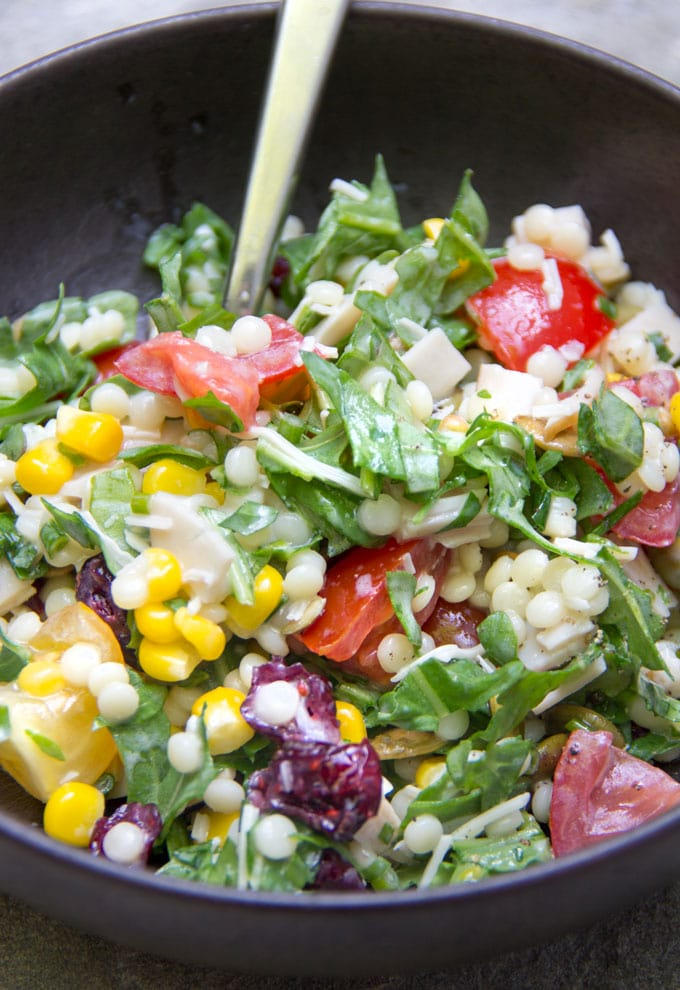 close-up of chopped salad with arugula, turkey, tomatoes, corn, couscous and cheese