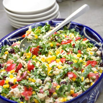 Colorful chopped salad in a blue oval bowl.