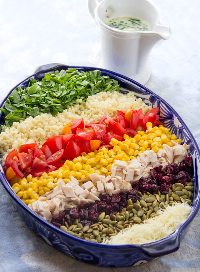 A chopped salad in an oval bowl, arranged on a rainbow of stripes, arugula, couscous, tomatoes, corn, turkey, cranberries, pumpkins seeds and cheese.