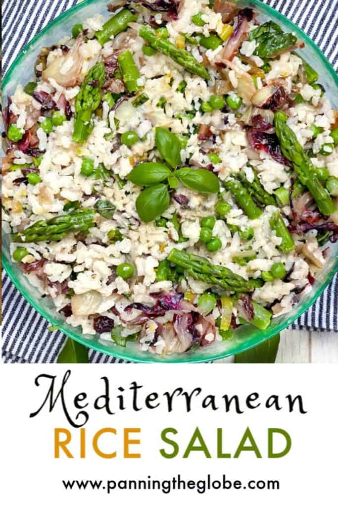 A green glass bowl filled with colorful Mediterranean rice salad with a sprig of basil in the middle