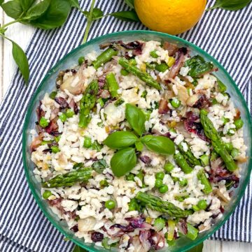 Mediterranean Rice Salad in a round green glass bowl with a sprig of basil in the middle