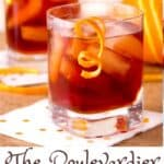 two deep red boulevardier cocktails with garnishes of swirly orange peel dangling from the glass