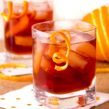 two deep red boulevardier cocktails with garnishes of swirly orange peel dangling from the glassThe Boulevardier is complex, refreshing and totally delicious - a fantastic drink recipe to add to your cocktail repertoire. With or without the smoke, these will be loved by all!