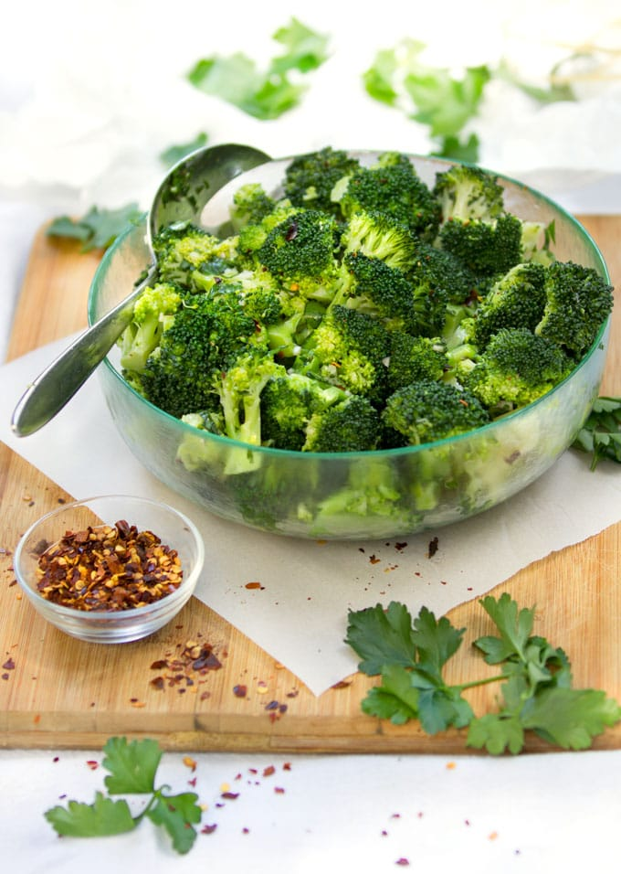 chimichurri broccoli salad in a bowl with a small bowl of crushed red pepper and some parsley leaves