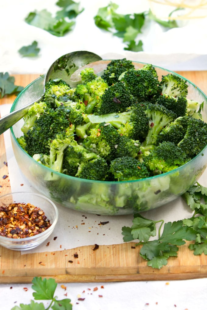 chimichurri broccoli salad in a green glass bowl, next to a small bowl of crushed red pepper flakes.